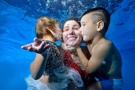 A young son and daughter kiss their mother from both sides while swimming underwater in the pool. They smile and play. The concept of a happy family. Portrait. Close-up. Horizontal view.
