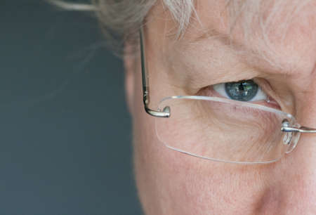 rimless: Mature woman with glasses looks stern  Stock Photo