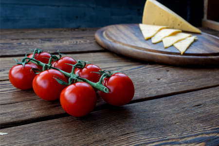 slice cheese and cherry tomatos on wooden cutting board