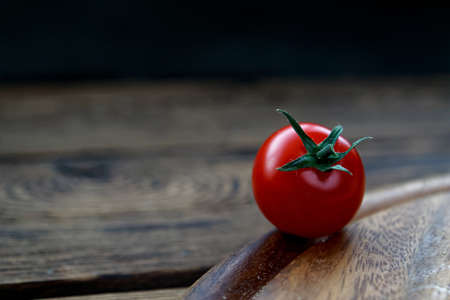 cherry tomatos on wooden cutting board
