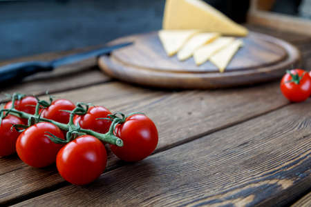 slice cheese and cherry tomatoes on a branch, lying on wooden cutting board Stock Photo