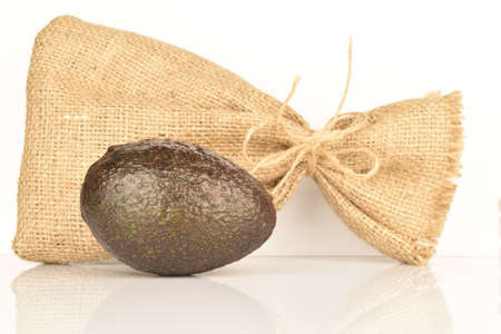 One whole, dark green, ripe aromatic delicious avocado, lie next to a jute bag. The background is white.