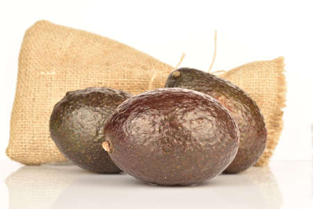 Three whole, dark green, ripe aromatic delicious avocados lie next to the jute bag. The background is white.