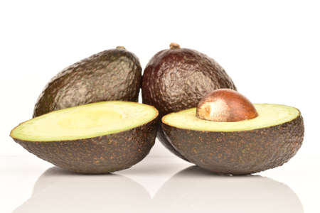 Two whole and two halves, dark green, ripe organic tasty avocado on a white background.