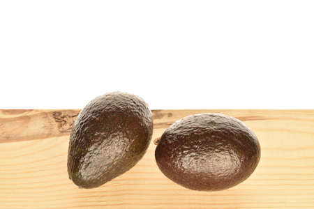 Two whole dark green rounded ripe tasty nutritious avocados lie on a wooden tabletop.
