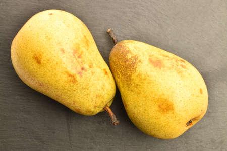 Ripe juicy, organic pears, close-up, on a slate board.