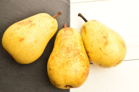Ripe juicy, organic pears, close-up, on a painted wooden table.