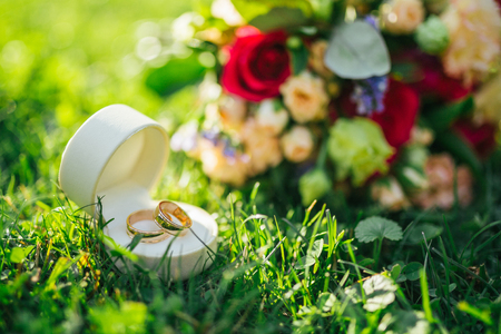 Wedding rings in a box lie next to a bouquet on the grass