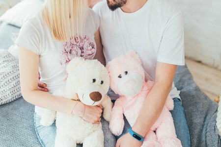Young beautiful couple sitting on the bed with teddy bears in hands Imagens