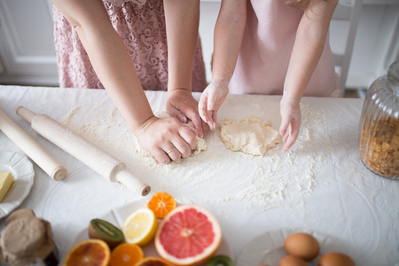 Daughter with mom knead dough for biscuits