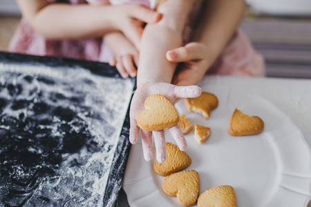 Mom and daughter lay out cookies on a white plate Imagens
