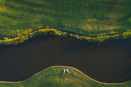 Frame shot from a drone a couple holding hands lying on the grass