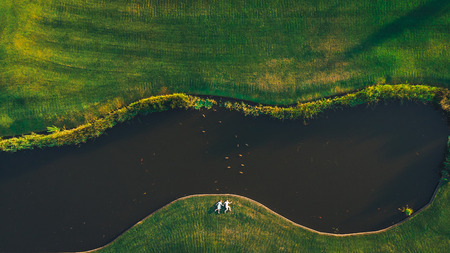 Top view of a couple laying on the grass near the river