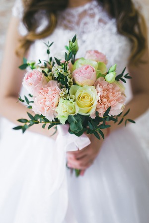 Beautiful bouquet with roses in the hands of the bride
