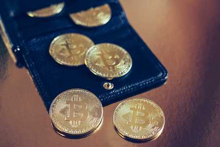 Bitcoins are scattered on the table from wallet