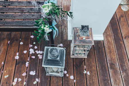 Wedding decorations, lanterns, benches, flowers and rose petals scattered on the floor
