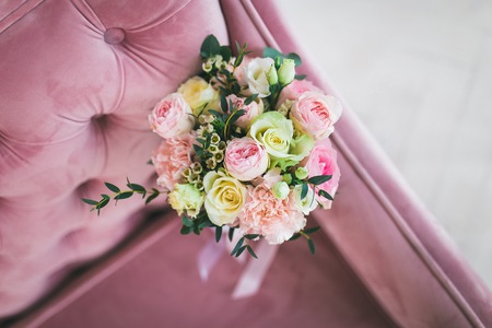 Beautiful bridal bouquet of pink and white roses on the sofa