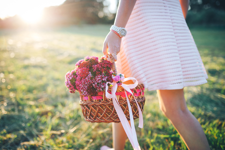 Girl walks across the field with a basket of flowers
