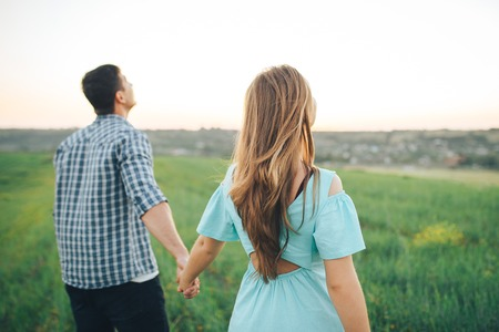 Young couple walking on the field holding hands