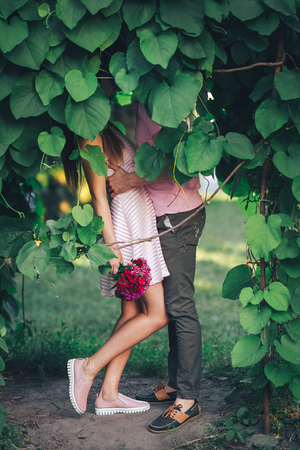 Couple kisses behind the leaves of a tree Imagens