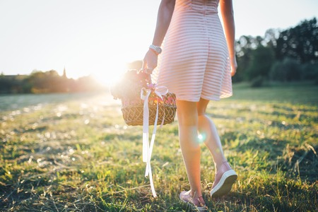 Girl with a basket of flowers in a pink dress Imagens