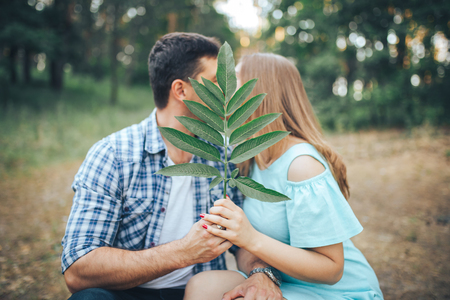 Young couple kissing in the forest while sitting on a cut branch