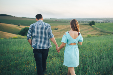 Young couple walking on the green grass in the field Imagens