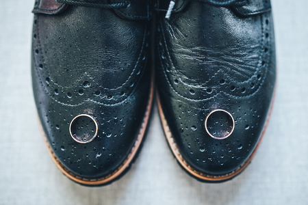 Wedding rings lie on the shoes of the groom