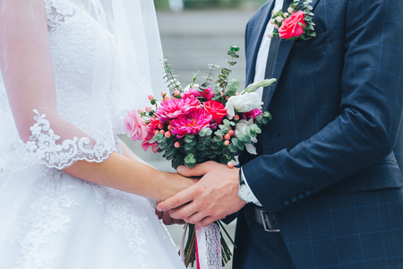 Bride and groom are holding a bouquet