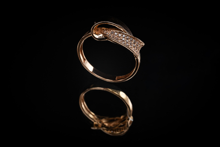 Wedding gold ring with a stones on a black background Imagens