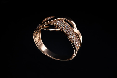 Wedding gold ring with a stone on a black background Imagens