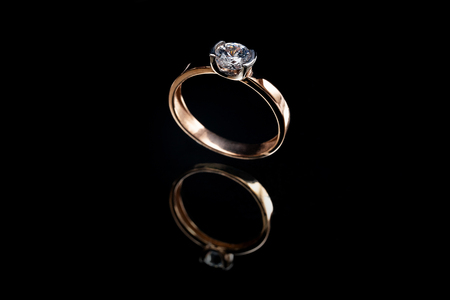 Golden ring with reflection with a big stone on a black background