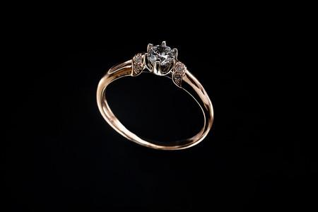 Goldener Ring mit einem großen Stein auf schwarzem Hintergrund