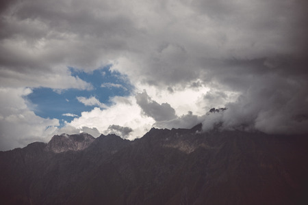 A view of the mountains shrouded in clouds through which the sunlight penetrates and the blue sky is visible Imagens
