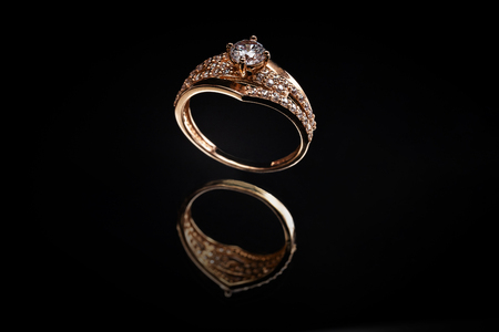 Gold ring with reflection on the mirror black background