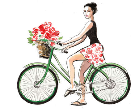 Pretty girl riding a bike with a basket of flowers