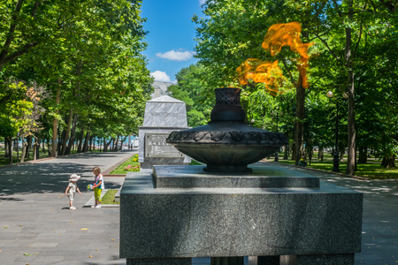 nikolay: NOVOROSSIYSK, RUSSIA - JULY 5, 2017: Little girls playing near The Eternal Flame and the tomb of Nikolay Sipyagin on Heroes Square