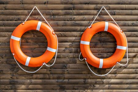 Two orange lifebuoys on hanging on a wooden wall of a boat station.