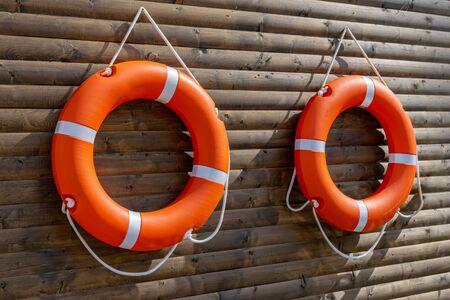 Dwa pomarańczowe koła ratunkowe na wiszące na drewnianej ścianie stacji łodzi. Zdjęcie Seryjne