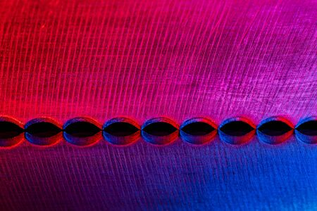 Macro image of the edge of blade of bread knife with reflection illuminated wred and blue