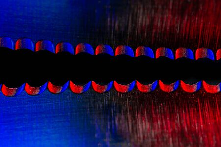 Macro image of the edge of blade of bread knife with reflection illuminated red and blue