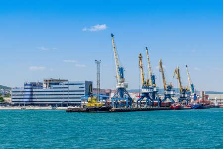 NOVOROSSIYSK, RUSSIA - JULY 17, 2019: The buildings of Novorossiysk the port administration and port cranes