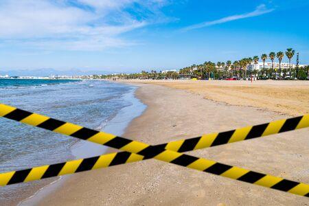 Yellow-black barrier tape against empty sand beach in Salou, Spain Фото со стока
