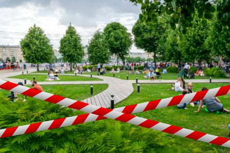 Barrier tape against blurred  of people relaxing in the park.