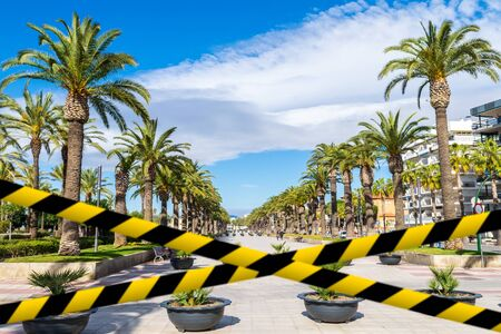 Barrier tape against the empty main promenade Passeig Jaume I of Salou, Spain Фото со стока