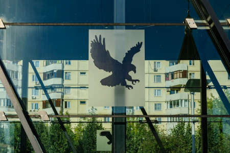Moscow, Russia - August 21, 2020: A silhouette of bird of prey on the glass wall of the entrance of Alma-Atinskaya metro station 新聞圖片