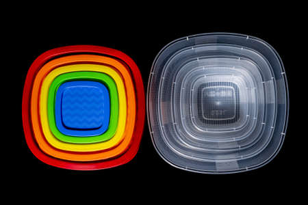 Set of plastic food containers with colorful lids isolated on black. 版權商用圖片