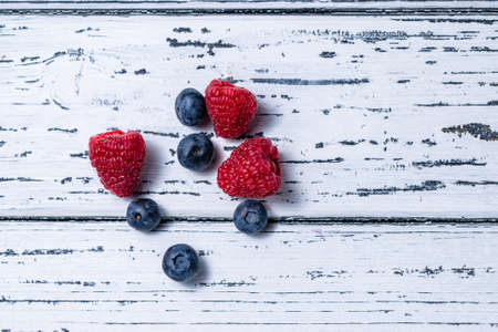 Raspberries and blueberries on an old white wooden background. Flat lay. Healthy food concept.