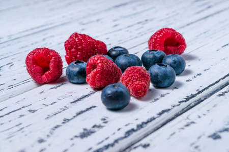 Raspberries and blueberries on an old white wooden background. Healthy food concept.