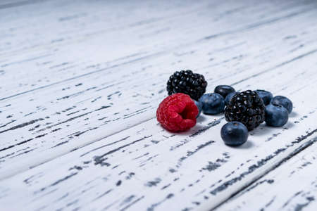 Raspberries, blackberries and blueberries on an old white wooden background. Healthy food concept.